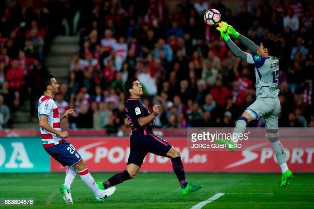 Granada's French defender Matthieu Saunier and Mexican goalkeeper Guillermo Ochoa vies with Barcelona's Uruguayan forward Luis Alberto Suarez during...