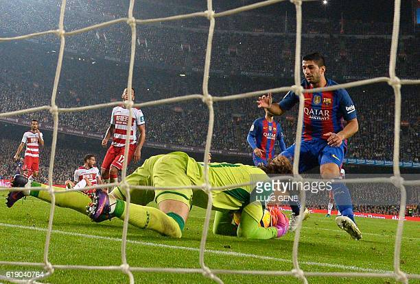 Granada's goalkeeper Guillermo Ochoa secures the ball in front of Barcelona's Uruguayan forward Luis Suarez during the Spanish league football match...