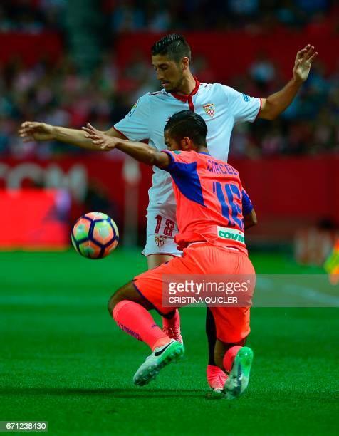 Granada's Moroccan midfielder Mehdi Carcela vies with Sevilla's defender Sergio Escudero during the Spanish league football match Sevilla FC vs...