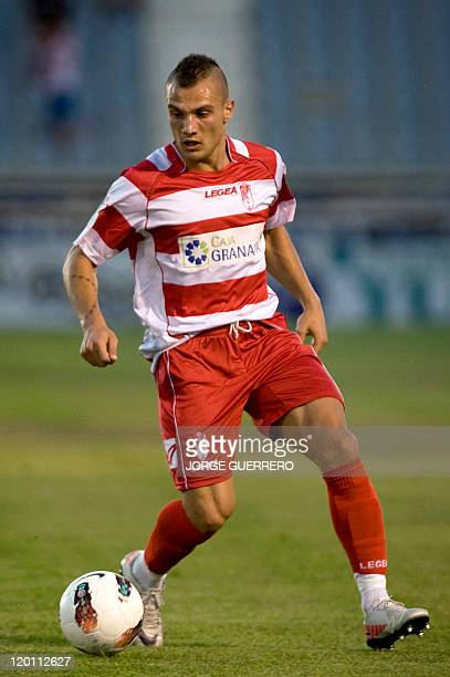 Granada's new football player French midfielder Yohan Mollo dribbles during a friendly football match between Granada CF and Real Jaen at the...