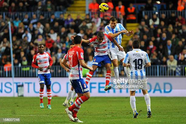 Granada's Nigerian forward Odion Ighalo vies with Malaga's midfielder Ignacio Camacho during the Spanish league football match Malaga CF vs Granada...