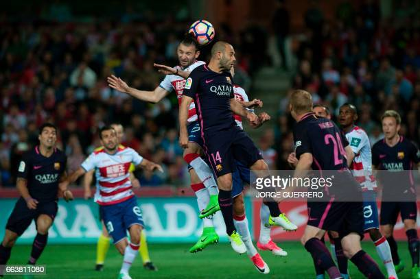 Granada's Uruguayan defender Gaston Silva vies with Barcelona's Argentinian midfielder Javier Mascherano during the Spanish league football match...