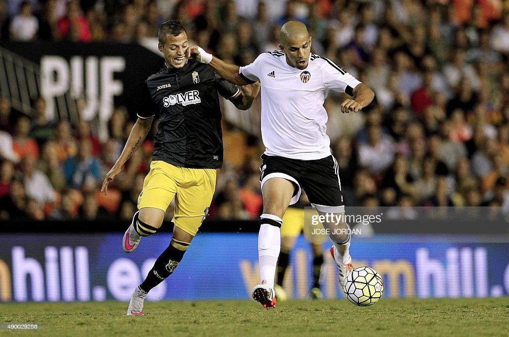 Granada's Uruguayan forward Nico Lopez vies with Valencia's French midfielder Sofiane Feghouli during the Spanish league football match Valencia CF...