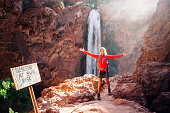 Image of Mooney Falls in the the Grand Canyon. A large Rocky landscape with a waterfall flowing down. A woman trekking stands with her arms spread out and smiling at the camera. A warning sign can be
