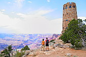 Grand Canyon people hiking. Hiker couple enoying view. Indian Desert View Watchtower, south rim of Grand Canyon, Arizona, USA with view over Colorado River.