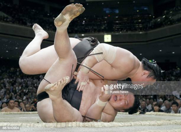 Grand champion Hakuho defeats ozeki Goeido with a clinical uwatehineri twisting overarm throw on the 11th day of the Summer Grand Sumo Tournament at...