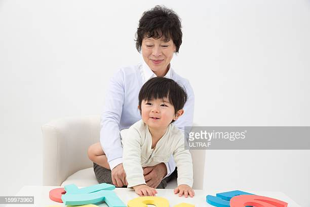 Grand mother and boy playing with boards of number