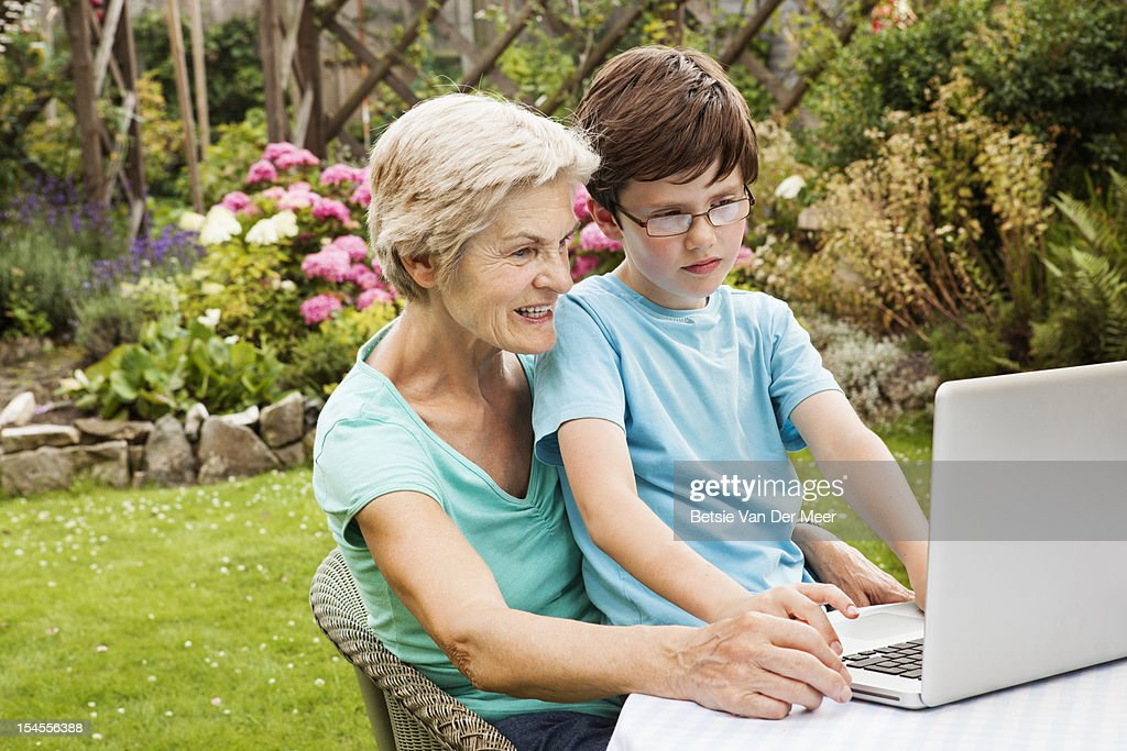 Grand mother and grandchild using laptop. : Stock Photo