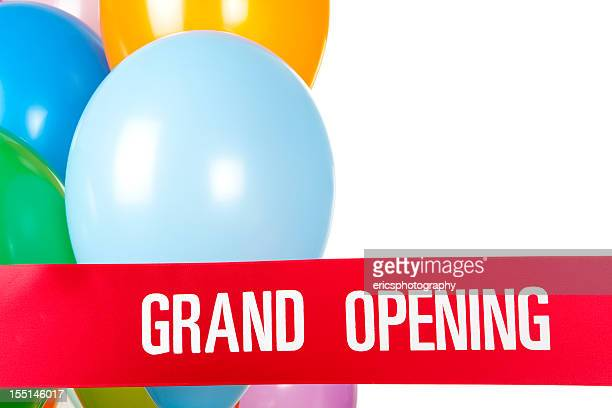 Grand opening ribbon and balloons on white