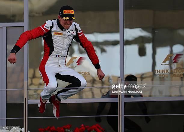 Grand Prix's French driver Esteban Ocon celebrates winning the 2015 title on the podium at the Yas Marina circuit in Abu Dhabi on November 29 2015...
