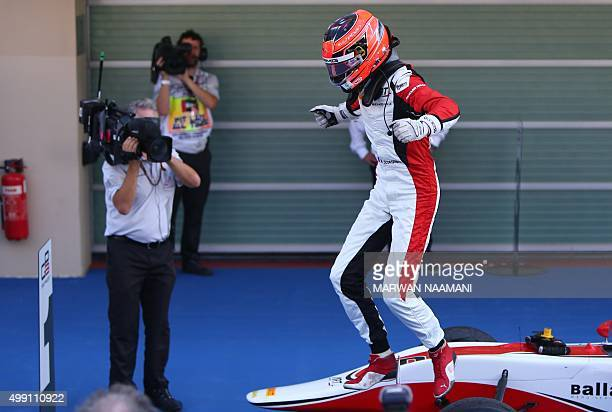 Grand Prix's French driver Esteban Ocon celebrates winning the 2015 title at the Yas Marina circuit in Abu Dhabi on November 29 2015 after the Abu...