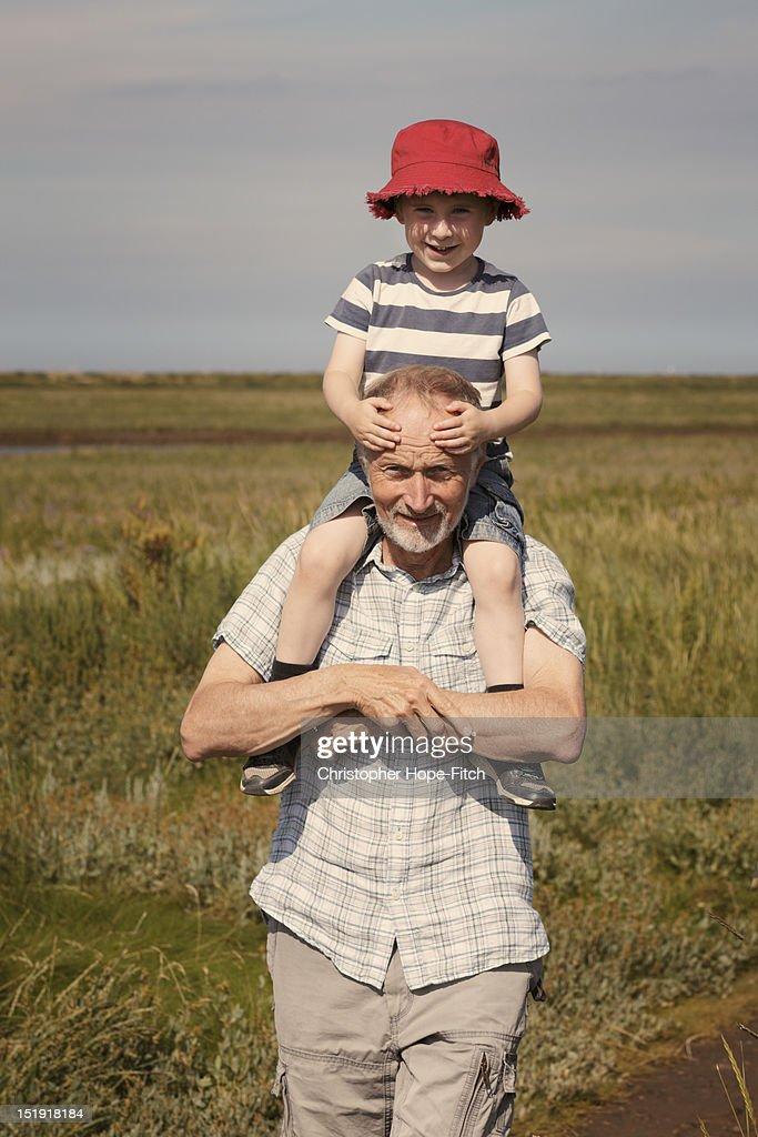 Grandad carrying grandson : Stock Photo