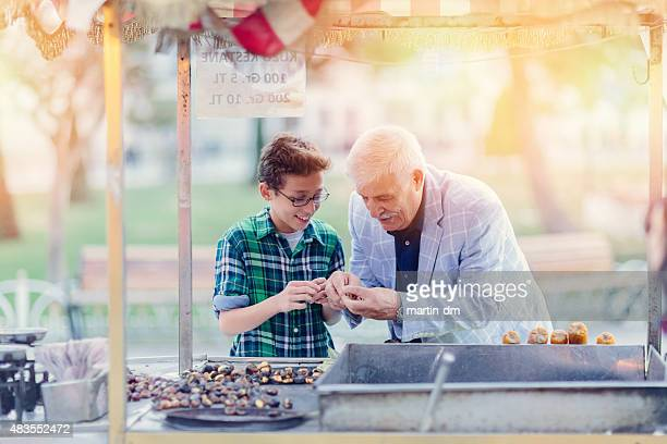 Grandafther and grandson buying roasted chestnuts