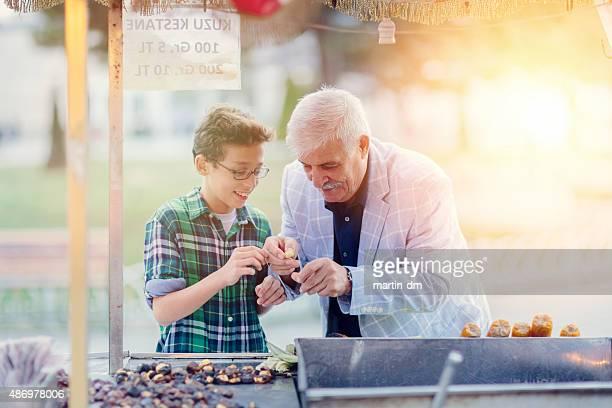 Grandafther acheter des marrons grillés et petit-fils