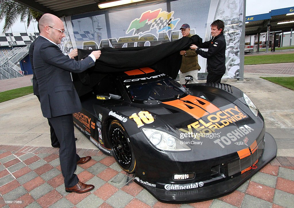 Grand-Am President/CEO Ed Bennett, Grand-Am Founder Jim France, Velocity Worldwide CEO Americas Paul Blakely, and car onwer Wayne Taylor help to unveil the #10 Wayne Taylor Racing Velocity Worldwide Corvette Dallara DP after a press conference announcing Velocity Worldwide as the team's new sponsor at Daytona International Speedway on January 3, 2013 in Daytona Beach, Florida.