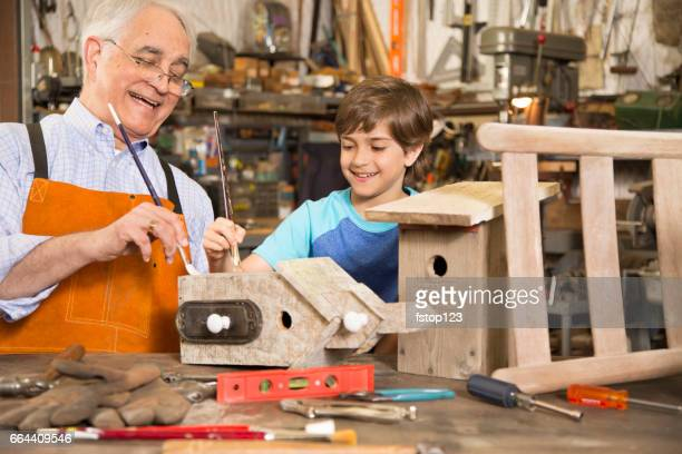Grandchild in workshop with grandfather building birdhouses.