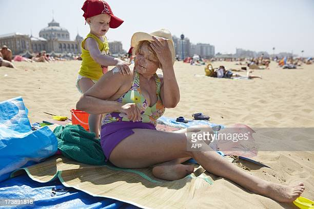 A grandchild protects his grandmother with sunscreen on a sunny day at the Scheveningen beach on July 18 2013 AFP PHOTO / ANP MARTIJN BEEKMAN...