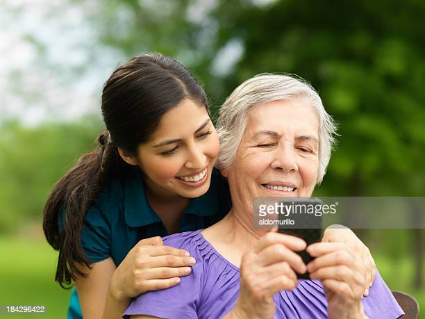 Grandchild teaching her grandmother how to use the cellphone
