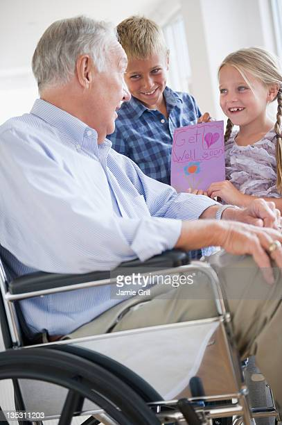 Grandchildren giving get-well card to grandfather