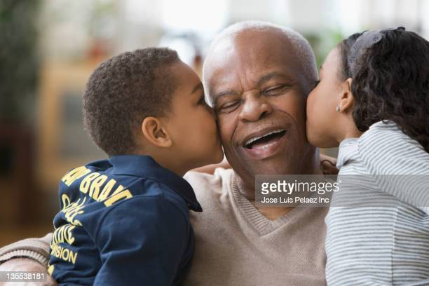 Grandchildren kissing grandfather