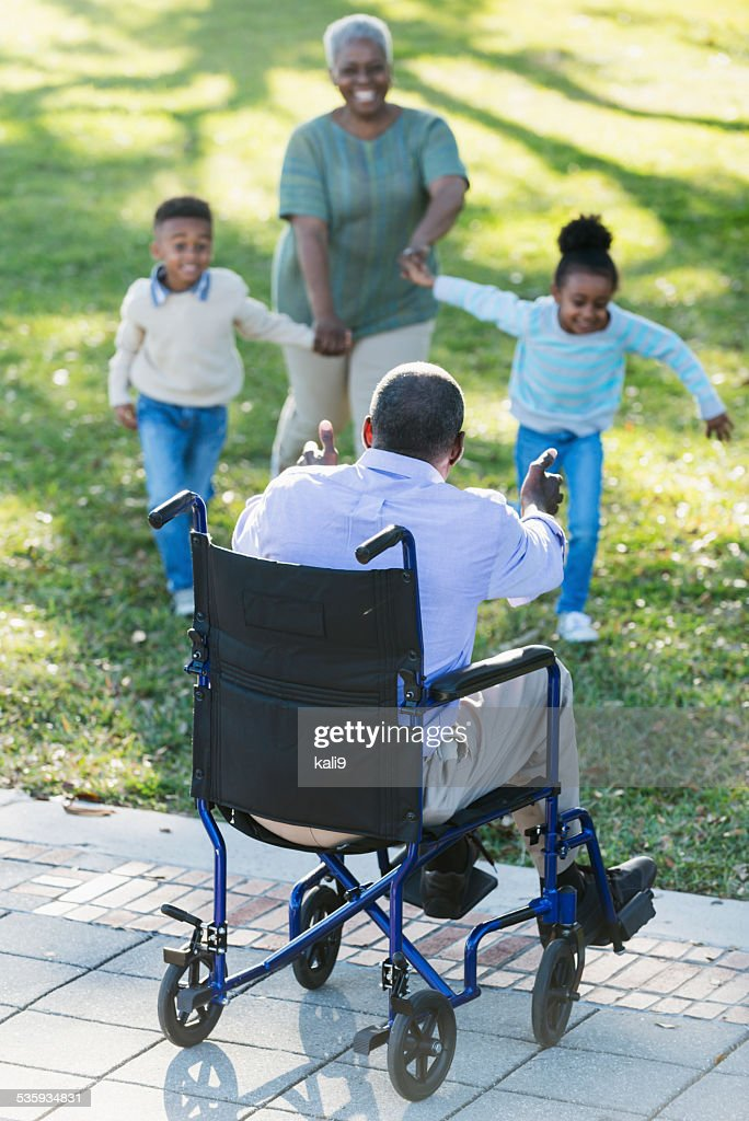Grandchildren running to grandfather in wheelchair : Stock Photo