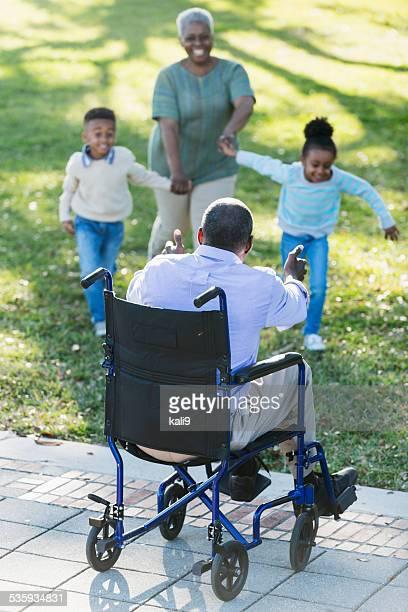 Petits-enfants courir à grand-père en fauteuil roulant