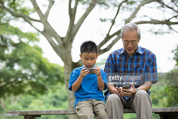 Granddad and grandson with smart phones