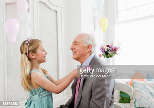 Granddaughter adjusting granddad's tie. : Stock Photo
