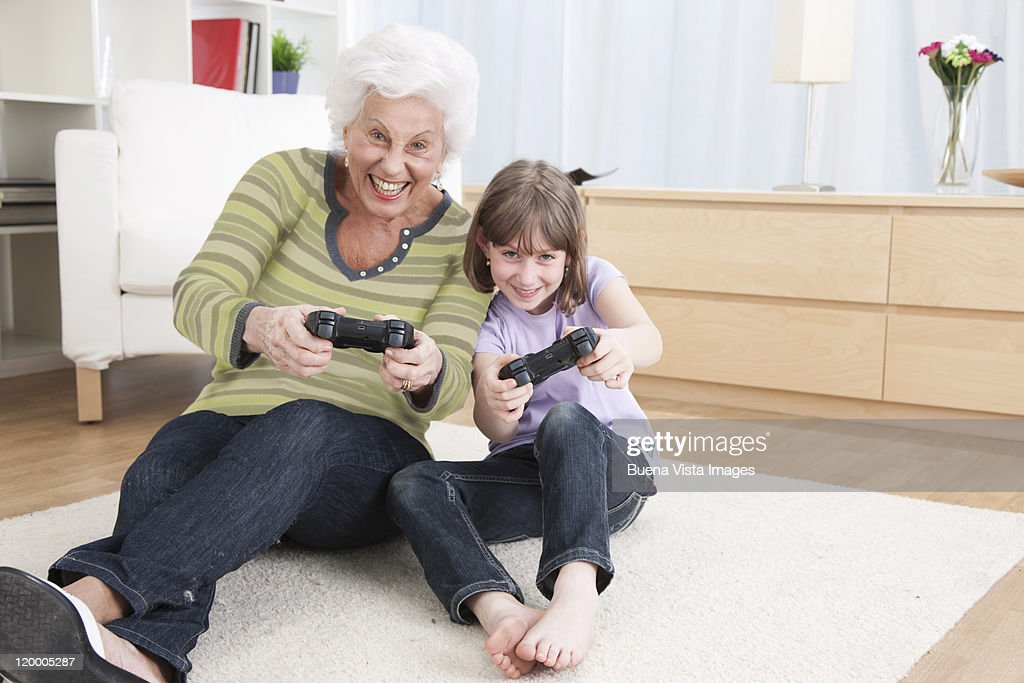 Granddaughter and grandmother playing game boy : Stock Photo