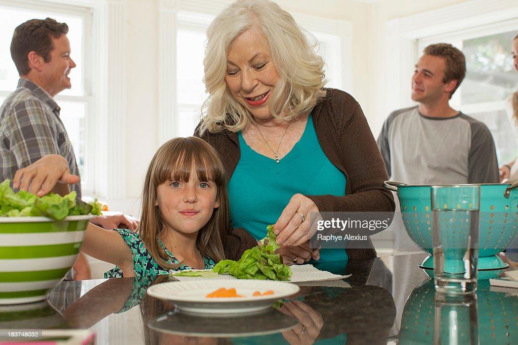Granddaughter and grandmother preparing salad : Stock Photo