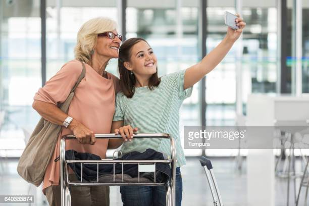Granddaughter and grandmother taking selfie before boarding.