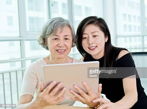 Granddaughter and grandmother using digital tablet