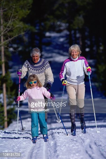 GOLYE046 Granddaughter and grandparents skiing : Stock Photo