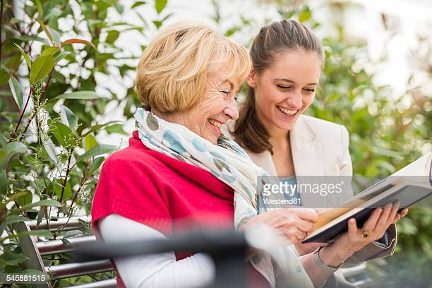 Granddaughter and her grandmother watching photo album