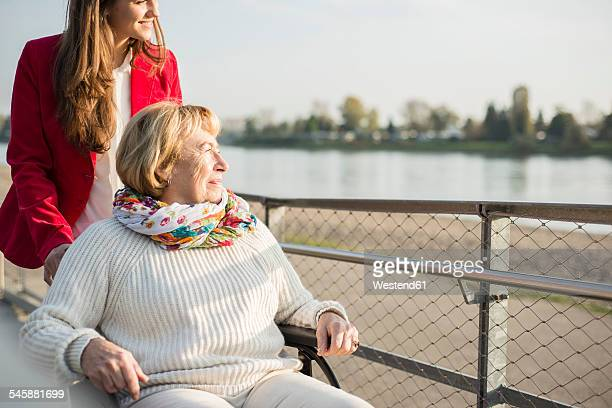 Granddaughter assisting her grandmother sitting in wheelchair