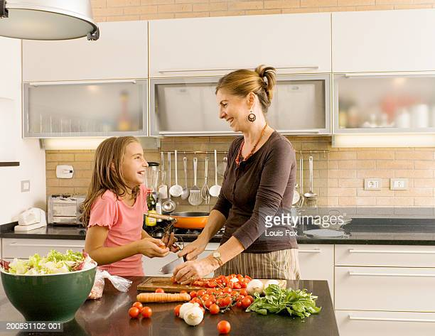 Granddaughter (8-12) cooking in kitchen with grandmother, smiling