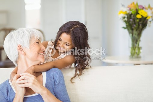 Granddaughter embracing her grandmother in living room : Stock Photo