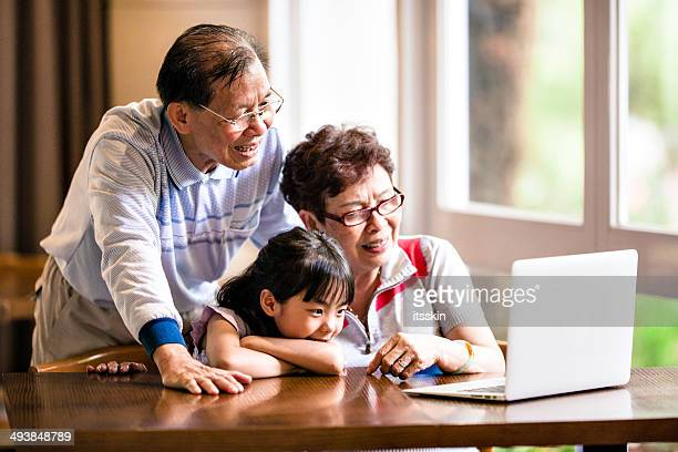 Granddaughter, grandfather and grandmother using laptop