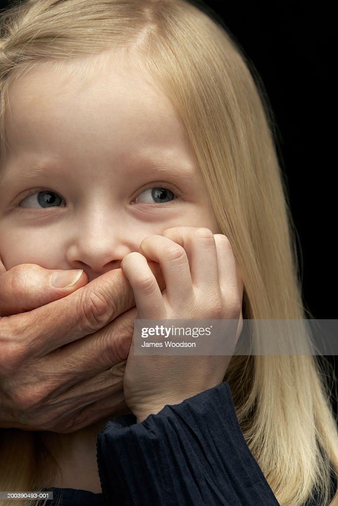 Granddaughter (5-7) having mouth covered by grandmother's hand : Stock Photo