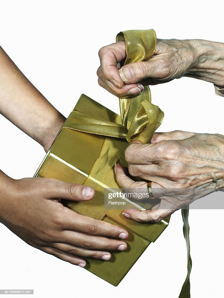 Granddaughter (6-7) holding gift and grandmother tying ribbon, close-up : Stock Photo