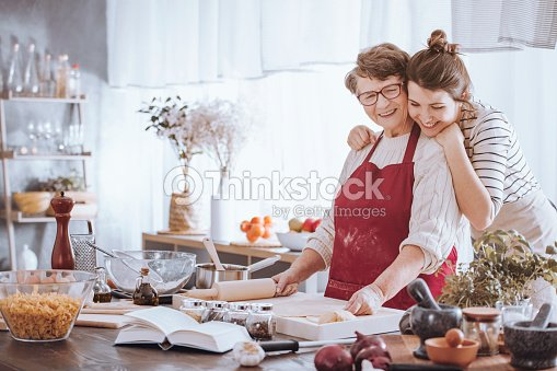 Granddaughter hugging grandmother in the kitchen : Stock Photo