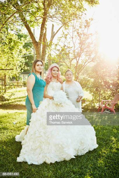 Granddaughter in quinceanera gown posing with mother and grandmother for photos in backyard