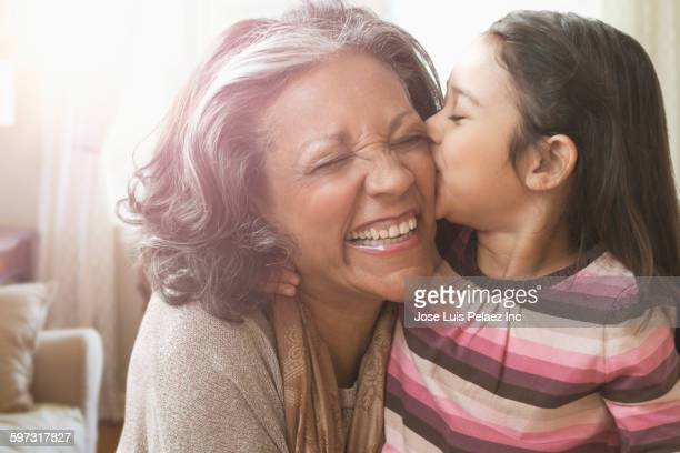 Granddaughter kissing cheek of grandmother