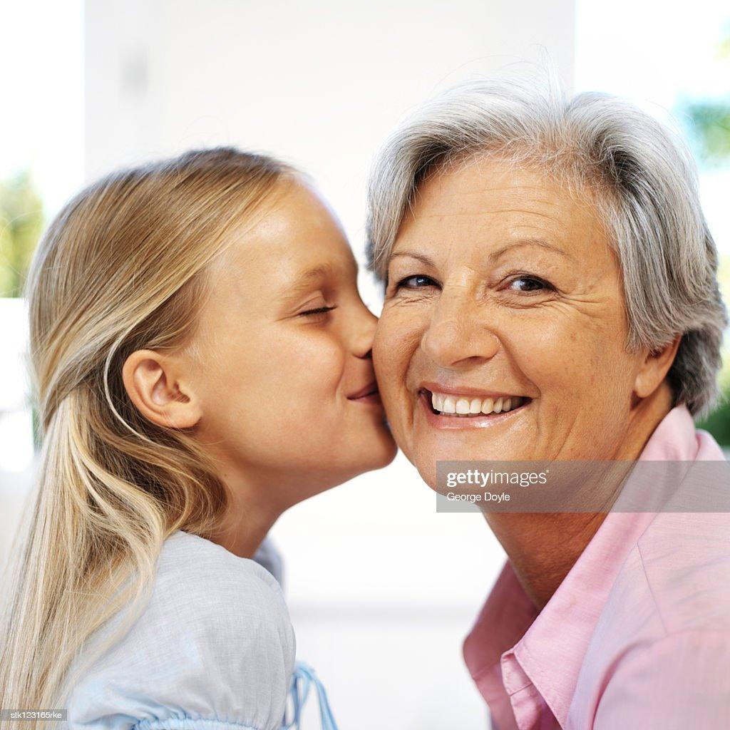 granddaughter kissing grandmother : Stock Photo