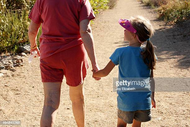 Granddaughter Looks Up at Grandmother on Walk