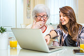 Granddaughter pointing at something on laptop screen to her grandma at home.