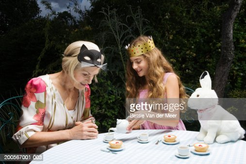 Granddaughter (10-11) pouring tea for grandmother at tea party in garden : Stock Photo