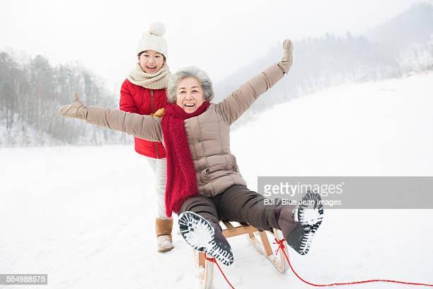 Granddaughter pushing grandmother on sled