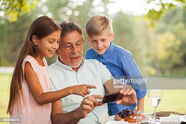 Nipote di insegnamento granddad di usare uno smartphone
