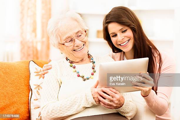 Granddaughter teaching her grandmother to use a tablet